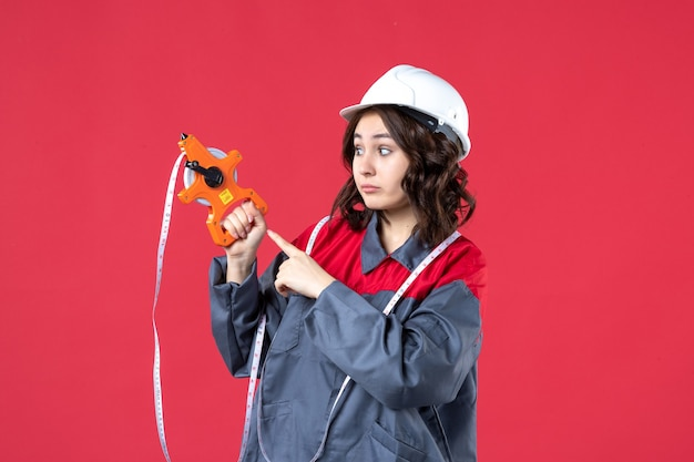 Vista ravvicinata del curioso architetto femminile in uniforme che indossa elmetto con nastro di misurazione sulla parete rossa