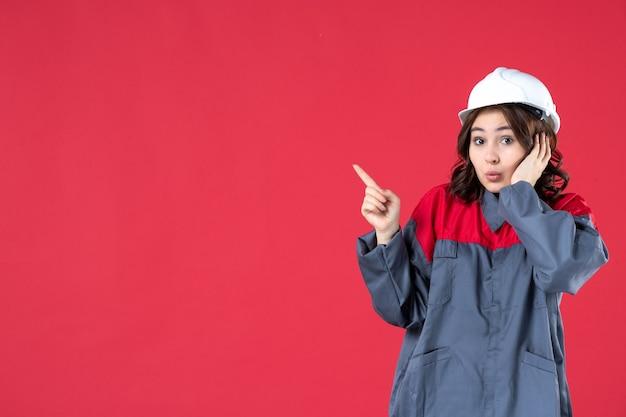 Vista ravvicinata del curioso costruttore femminile in uniforme con elmetto e indicando qualcosa sul lato destro sulla parete rossa isolata