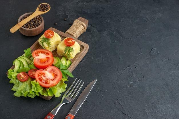 Vista ravvicinata di pomodori freschi tagliati e formaggio di cetrioli su tavola di legno posate su asciugamano di colore scuro sul lato destro sulla superficie nera