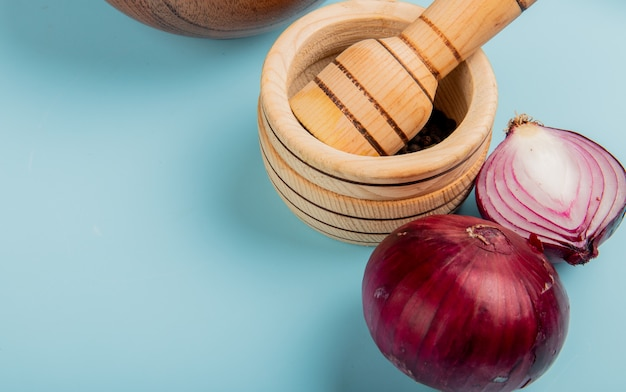 Close-up view of cut and whole red onions and black pepper seeds in garlic crusher on blue background