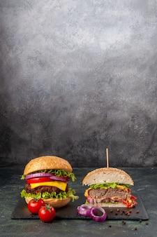 Vista ravvicinata di interi gustosi panini e pomodori tagliati con cipolle a stelo su vassoio nero su superficie di colore misto scuro
