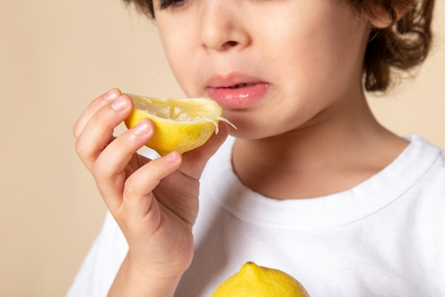 Close up, view cute kid eating sour lemon on pink