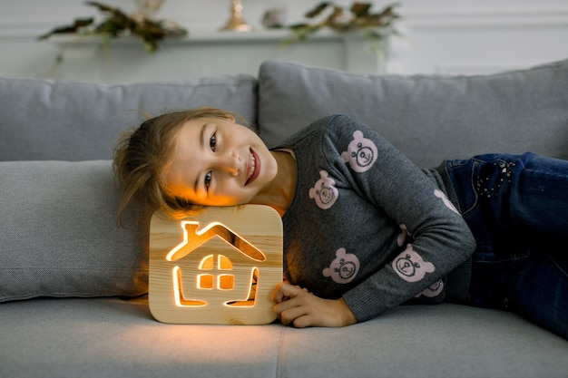 Close up view of cute little 10 years old girl in casual wear, lying on gray sofa at home and leaning her her head on beautiful stylish wooden night lamp. children and night lamps promo.