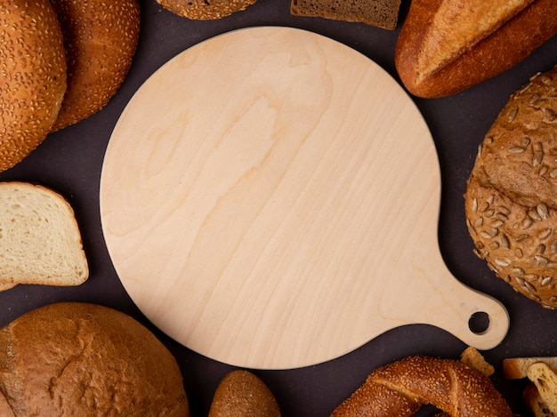 Close-up view of cutting board with breads around as cob bagel baguette on maroon background
