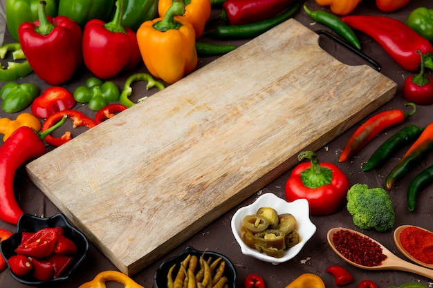 Close-up view of cutting board with peppers, broccoli and sumac around