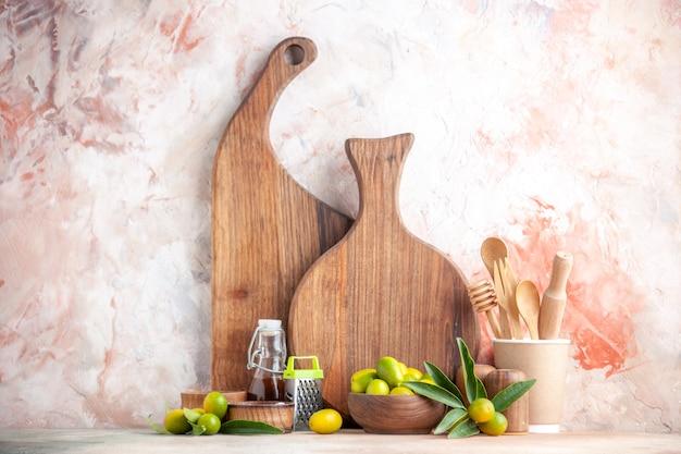 Vista ravvicinata di taglieri cucchiai di legno grattugia bottiglia di olio e kumquat freschi su superficie colorata