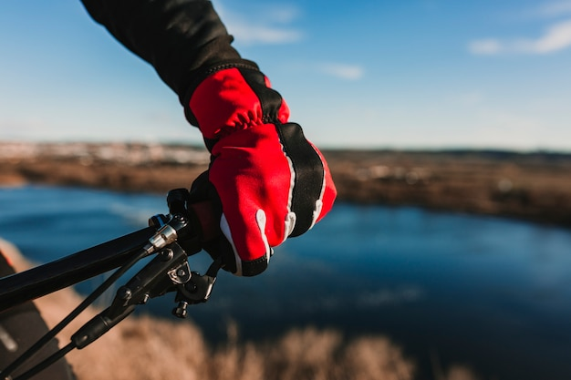 Close up view of a cyclist equipment glove and handlebar. man riding the bike down rocky hill at sunset. extreme sport concept.