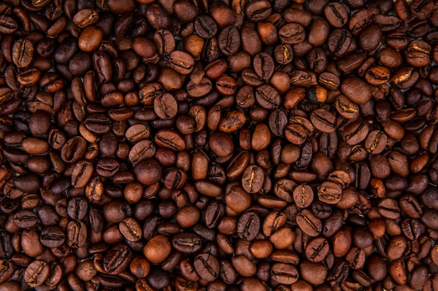 Close up view of dark fresh roasted coffee beans on coffee beans background