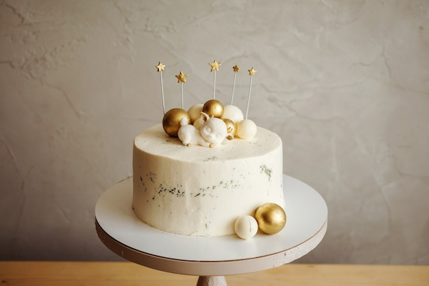 Close up view of delicious birthday cake with golden balls and deer symbol