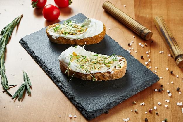Крупным планом вид вкусные брускетты с сыром и microgreen на деревянной поверхности