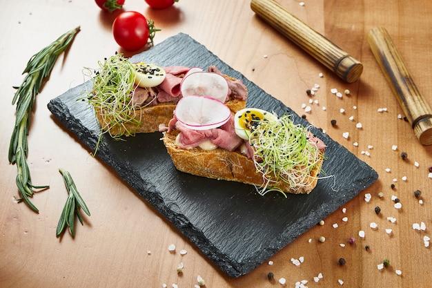 Крупным планом вид вкусные брускетты с ростбифом и помидорами на деревянной поверхности