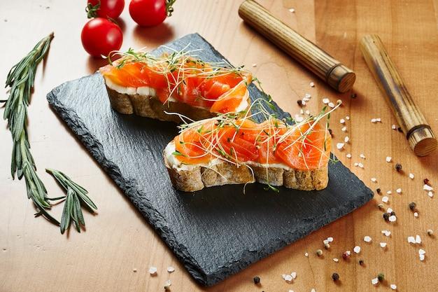Крупным планом вид вкусные брускетты с лососем и microgreen на деревянной поверхности