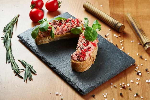 Крупным планом вид вкусные брускетты с тунцом и микрогрин на деревянной поверхности