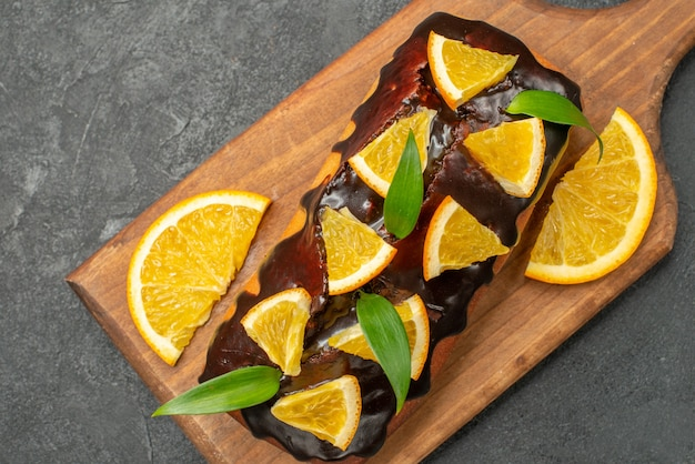 Close up view of delicious cakes decorated with orange and chocolate on cutting board on black table