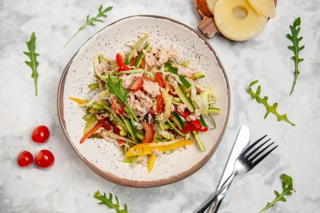 Vista ravvicinata di una deliziosa insalata di pollo con verdure pomodori ananas essiccati posate su superficie bianca macchiata