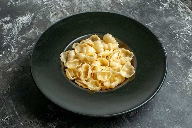 Close up view of delicious conchiglie on a black plate on gray background