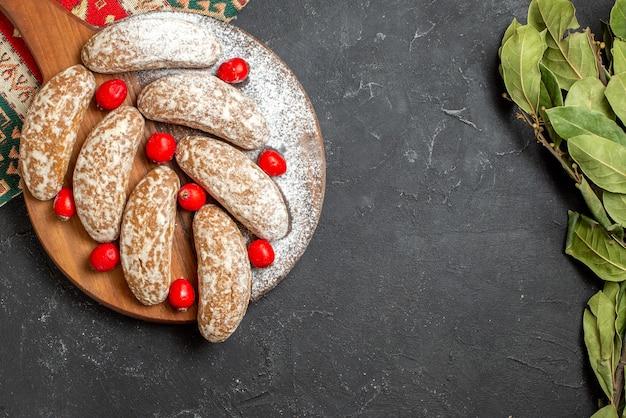 Vista ravvicinata di deliziosi biscotti su un tagliere marrone con bacche di cornell rosse su oscurità