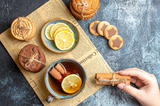 Close up view of delicious cookies and hand holding a cup of black tea with cinnamon on an old newspaper on dark background