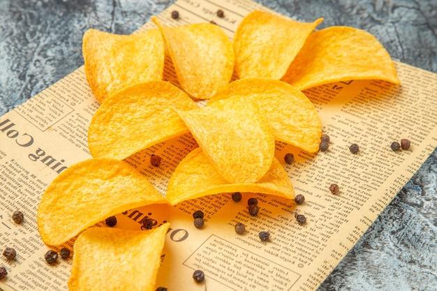 Vista ravvicinata di deliziose patatine fatte in casa sul giornale sulla tabella grigia