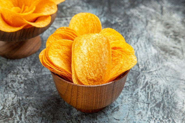 Close up view of delicious homemade potato chips on gray table