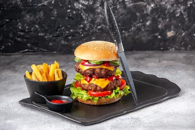 Vista ravvicinata di deliziosi panini fatti in casa e patatine fritte ketchup verde su lavagna nera su superficie isolata grigia in difficoltà