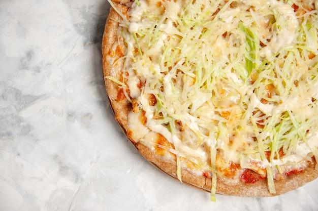 Vista ravvicinata di una deliziosa pizza vegana fatta in casa su una superficie bianca macchiata con spazio libero