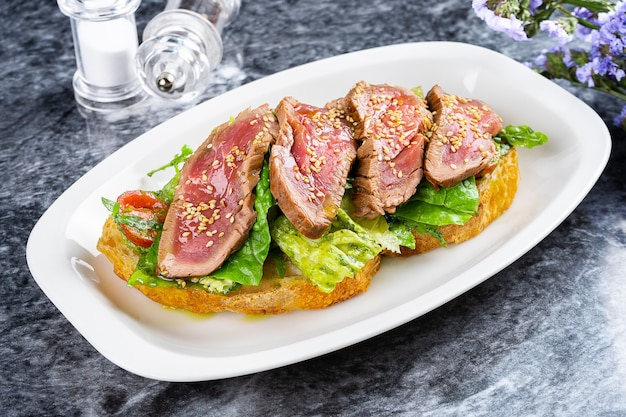 Close up view on delicious italian bruschetta with roast beef, lettuce, cherry tomato and sauce