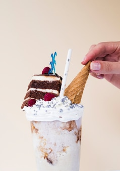 Close-up view of delicious milkshake with ice cream cone and cake