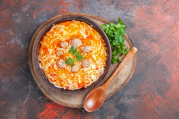 Vista ravvicinata di una deliziosa zuppa di noodle con pollo e verdure su tagliere di legno su sfondo scuro