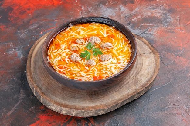 Vista ravvicinata di una deliziosa zuppa di noodle con pollo su tagliere di legno su sfondo scuro