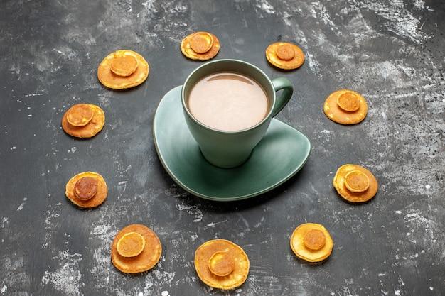 Vista ravvicinata del delizioso pancake intorno a una tazza di caffè su grigio