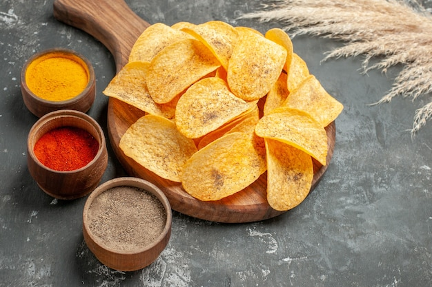 Close up view of delicious potato chips spices with ketchup on gray table