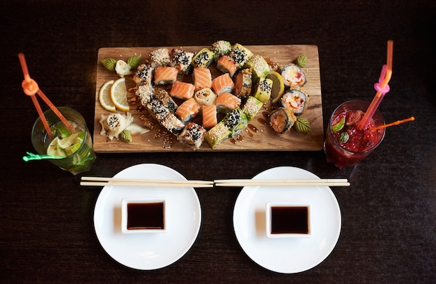 Close-up view of delicious rolling sushi served on the wooden board with chopsticks, soy sauce and cocktails