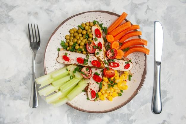 Vista ravvicinata di una deliziosa insalata con vari ingredienti su un piatto e posate su una superficie bianca con spazio libero