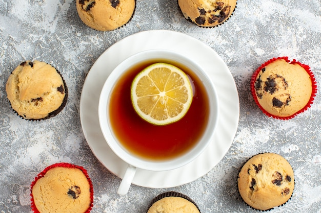 Close up view of delicious small cupcakes with chocolate around a cup of black tea on ice surface