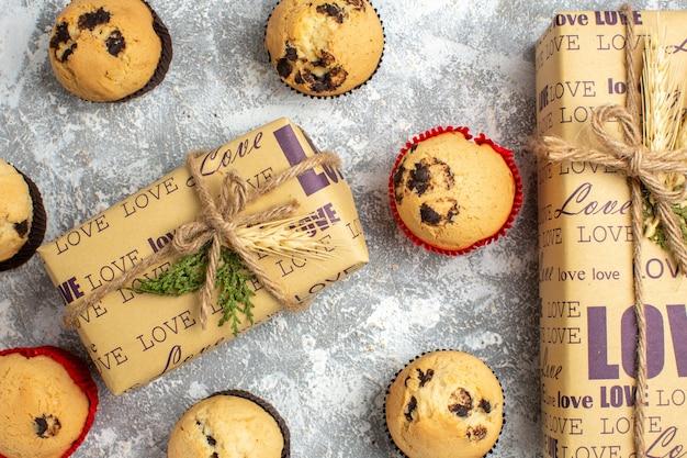Vista ravvicinata di deliziosi piccoli cupcakes con cioccolato intorno a un regalo con iscrizione d'amore sulla superficie del ghiaccio