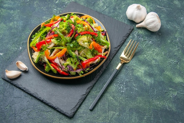 Close up view of delicious vegetable salad with various ingredients on black cutting board