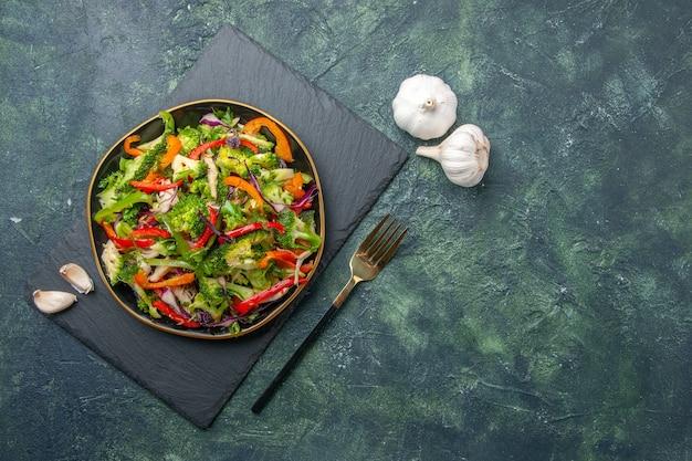 Vista ravvicinata di deliziosa insalata di verdure con vari ingredienti su tagliere nero