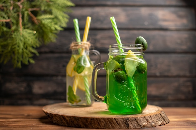 Close up view of detox water and fresh juice on brown wooden background
