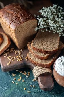 Vista ravvicinata dei frumenti del pane nero dietetico sul tagliere di legno farina di uova di fiori in una ciotola su sfondo blu