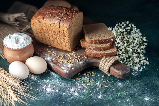 Vista ravvicinata dei frumenti del pane nero dietetico sul tagliere di legno farina di uova di fiori in una ciotola su sfondo blu sfocato