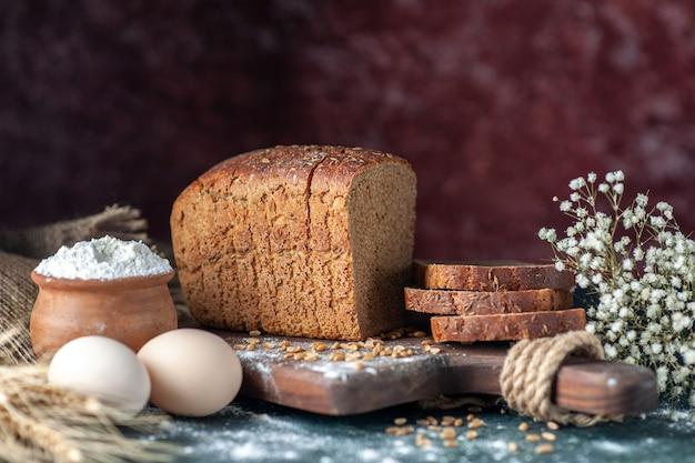 Vista ravvicinata dei frumenti del pane nero dietetico sul tagliere di legno farina di uova di fiori in una ciotola su sfondo sfocato