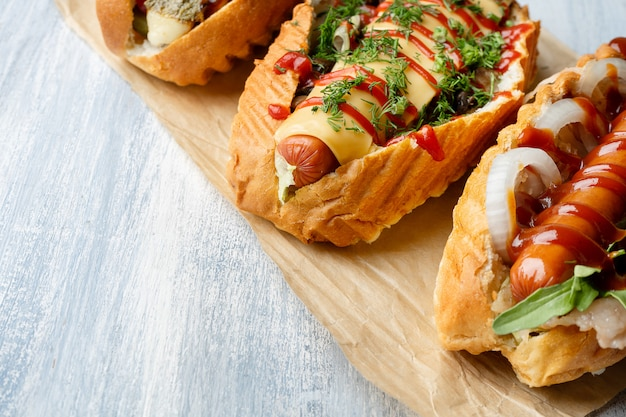 Close up view on different food styled hot dogs with toppings on light wooden surface