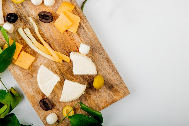 Close-up view of different kinds of cheese with grape pieces olives on cutting board on white decorated with flowers and leaves with copy space