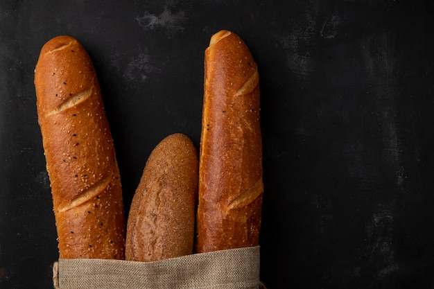 Close-up view of different types of baguette on left side and black background with copy space