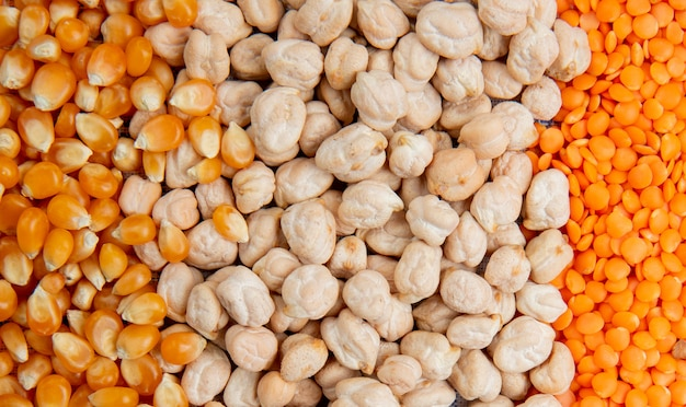 Close up view of different types of groats corn seeds chickpeas red lentils