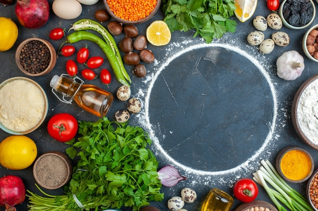 Vista ravvicinata della cena che cucina con uova verdure fresche spezie uova bottiglia di olio caduta fasci verdi bottiglia di olio caduta
