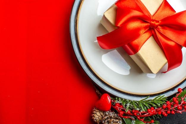 Vista ravvicinata di piatti da pranzo con regalo su di esso e rami di abete con cono di conifera accessorio decorazione su un tovagliolo rosso