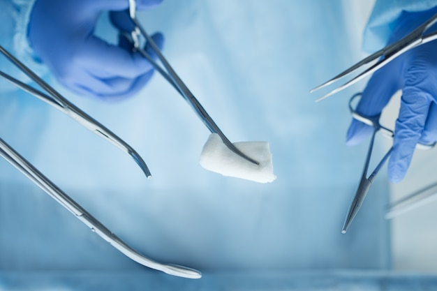 Close up view of doctor hands holding surgical tools. group of surgeons operating patient in surgical theatre. surgery and emergency concept
