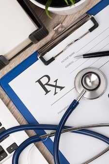 Close-up view of doctor working table. stethoscope, laptop and blank prescription form. top view